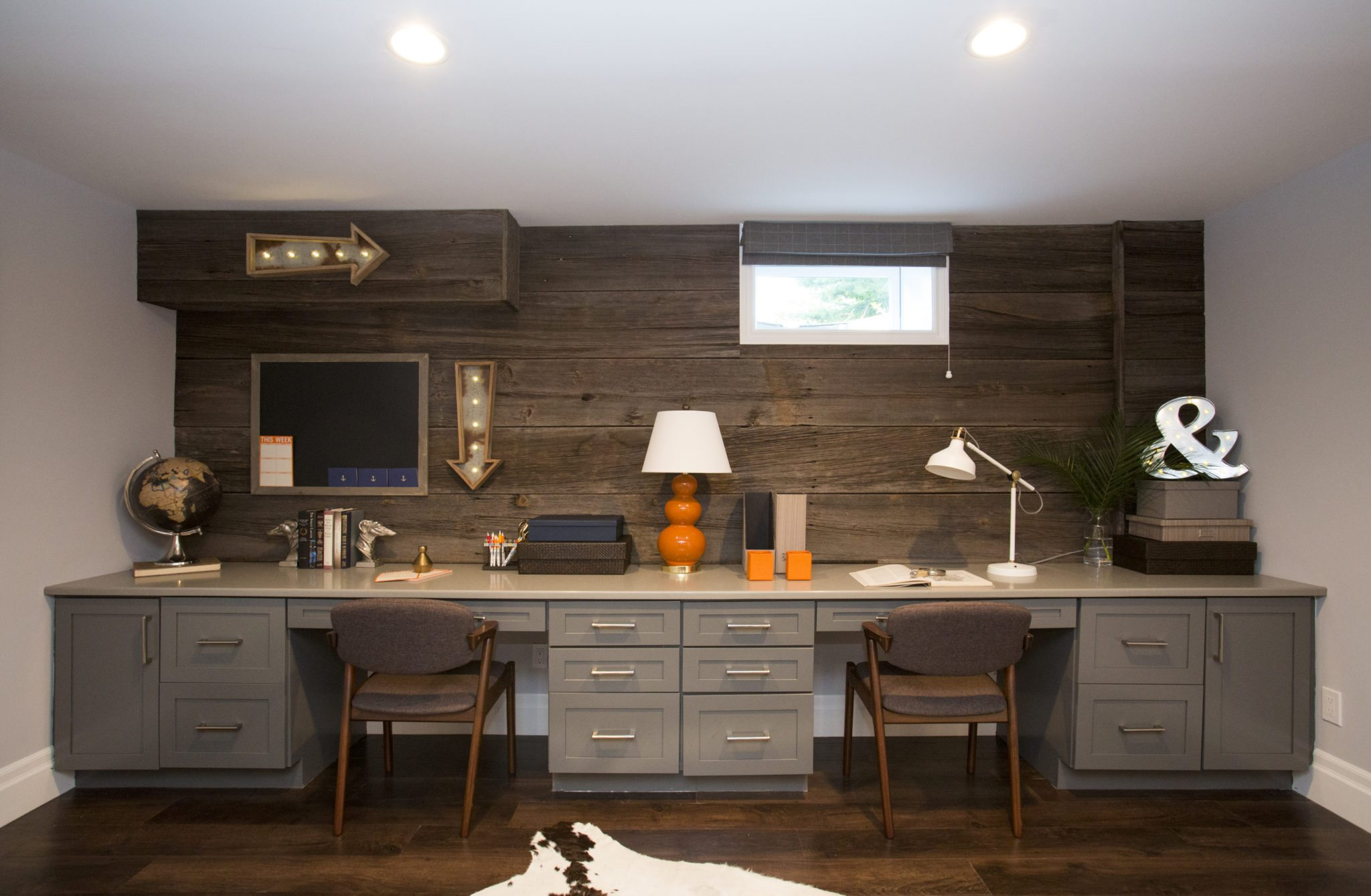 Basement - After 6: After the renovation, the basement in Charlie and Renee Mattiello's current home in Katonah, New York, is a combination office and entertaining space. Along one wall is a double desk, and a cozy seating area complete with a bar tray is staged on the other side of the room, as seen on Buying & Selling. (After)